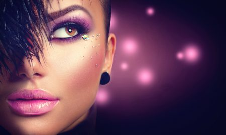 Sexy model girl face closeup with holiday bright purple makeup